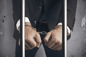 Concept of handcuffed businessman in jail